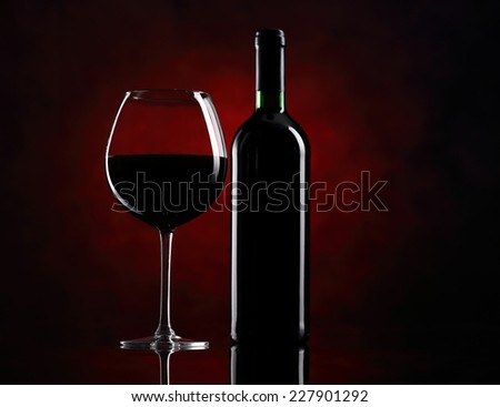 Red wine glass with bottle on the red background