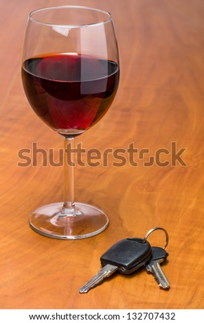 Red wine glass with car keys - stock photo