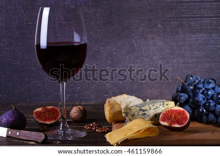 Red wine glass with fruits, cheese, figs and nuts on dark wooden background. Copy space.
