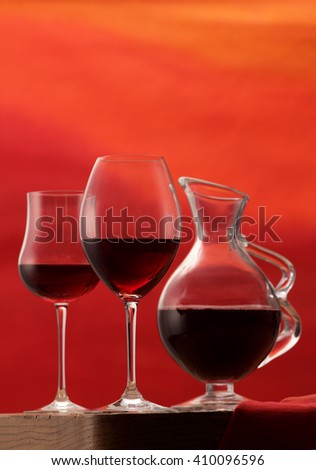 Red wine glasses and wine carafe isolated on red  background