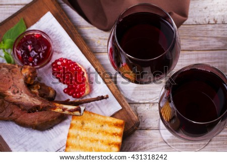 Red wine glasses. Rack of lamb with pomegranate sauce and greens. View from above, top studio shot