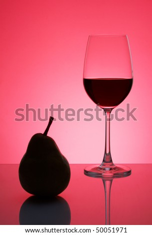 Red wine in a glass with a pear on a red background - stock photo