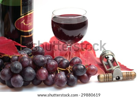 Red wine in a glass with grapes, leaves, wine bottle and cork screw over white background