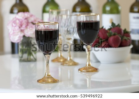 Red wine in a glasses on white table background.