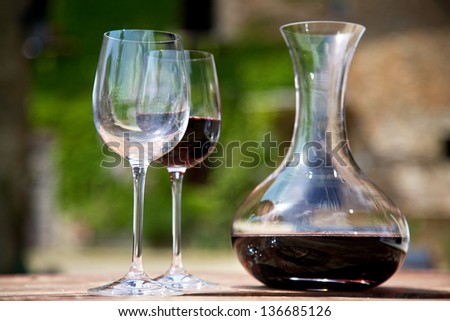 Red wine in a wine carafe and a two wine glasses in old vineyard - stock photo