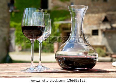 Red wine in a wine carafe and a two wine glasses in the vineyard - stock photo