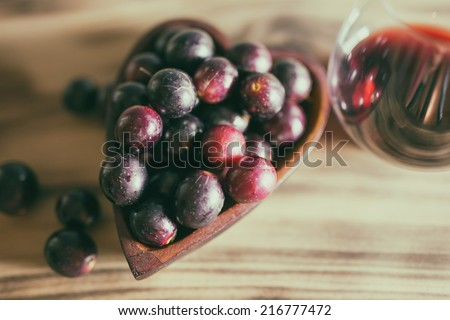 Red wine in crystal stemless glass with wooden heart shaped bowl filled with Muscadine grapes on burned wooden background.  - stock photo