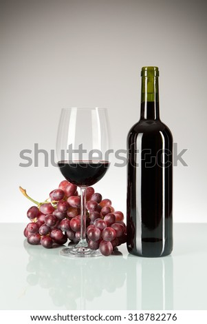 Red wine in glass and bottle with red grapes