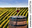 Red Wine in glass on wood barrel with vineyard background - stock photo