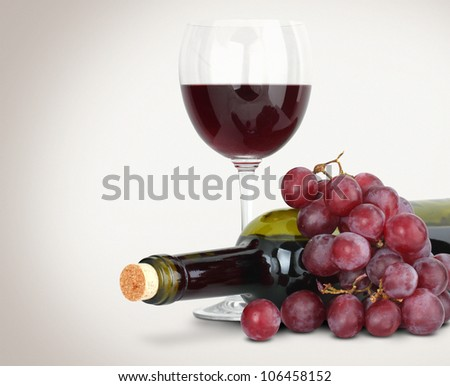 Red wine in glass with grapes and bottle