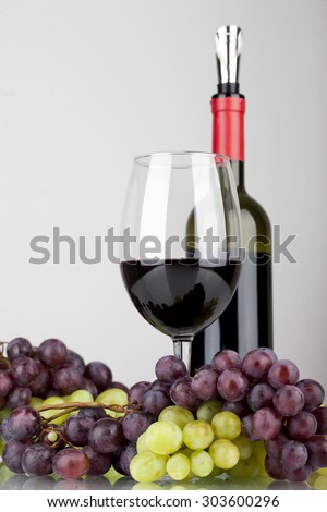 red wine in glass with grapes isolated on white background - stock photo