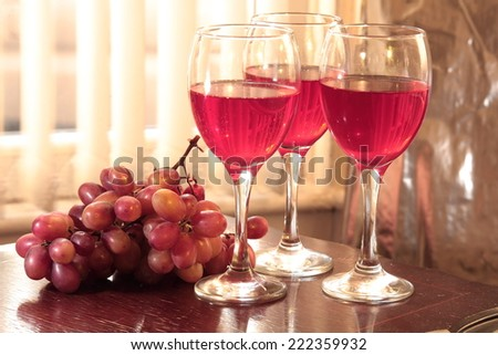 Red wine in glasses and grapes on wooden table.