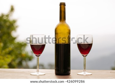Red wine in glasses with bottle, outdoor - stock photo