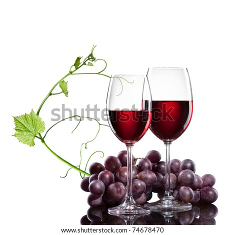 Red wine in glasses with grape and rod isolated on white - stock photo