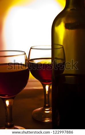 red wine in two glasses on a red background - stock photo
