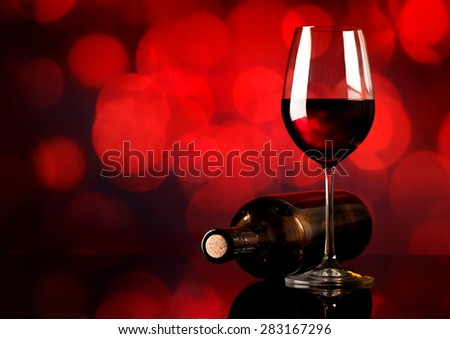 Red wine in wineglass and bottle on red background