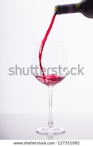 Red wine is being poured into a big wine glass.