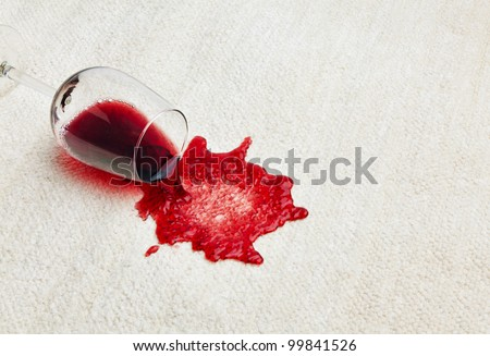 red wine is spilled on a carpet. reverse glass and all related - stock photo