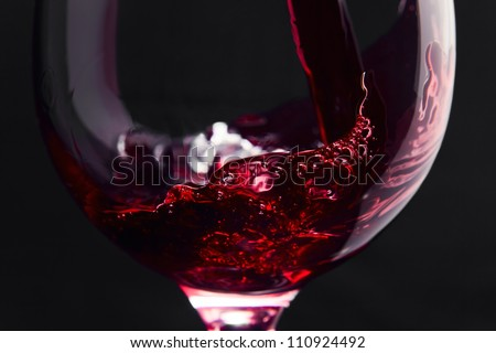 Red wine on a black background, abstract splashing. - stock photo