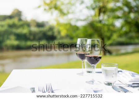 red wine on table set and  green grass background in the garden - stock photo