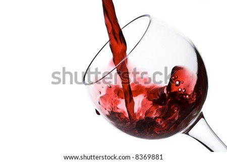 Red wine pouirng down into a wine glass isolated on white - stock photo