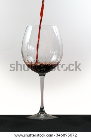Red wine poured in a clear glass standing on a black table-cover,isolated on white  - stock photo