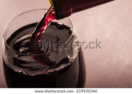 Red wine poured into a glass on background - stock photo
