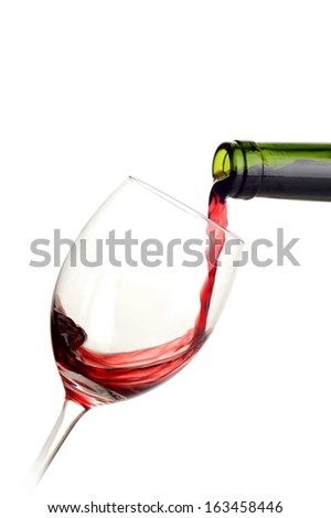 Red wine poured into a glass on white background
