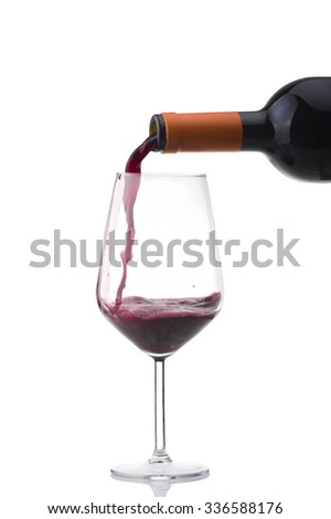 red wine poured into the glass on white  - stock photo