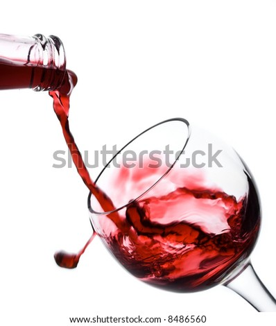 Red wine pouring down in a wine glass isolated on white - stock photo