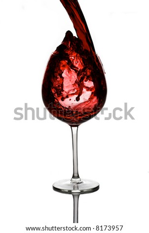 Red wine pouring down into a wine glass - stock photo