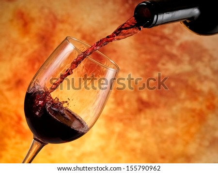 Red wine pouring from a bottle - stock photo