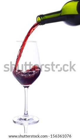 Red wine pouring from bottle into big glass on white background - stock photo