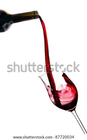 Red wine pouring from bottle, isolated on white background