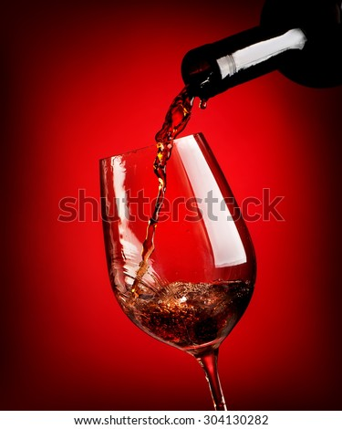 Red wine pouring in a wineglass on a red background - stock photo