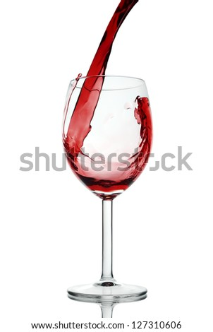 Red wine pouring in isolated wineglass