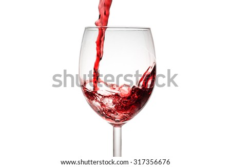 Red wine pouring in wine glass - stock photo
