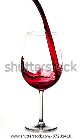 Red wine pouring into glass, isolated on white background - stock photo