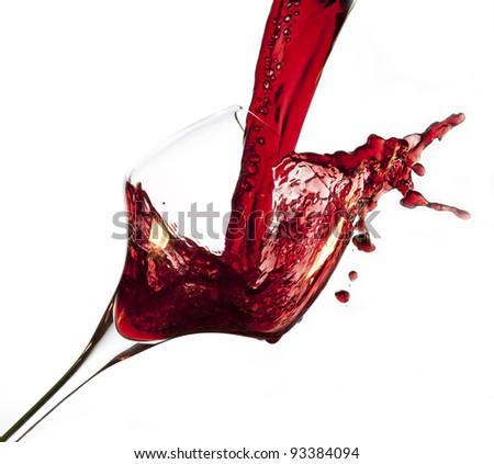 Red wine pouring into glass, isolated on white background