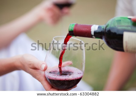 Red wine pouring into wine glass - stock photo