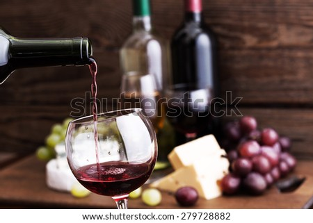 Red wine pouring into wine glass, close-up. Cheese, grapes and wine bottles on wooden table in restaurant. Flat mock up for design