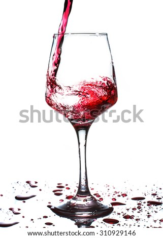 red wine pouring into wine glass isolated on white