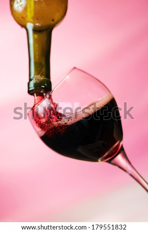 Red Wine pours into, onto, and around a wine glass filling it, spilling it and making a mess all over. Photographed with a fast shutter speed of up to 4000th of a second for beautiful stop motion.  - stock photo