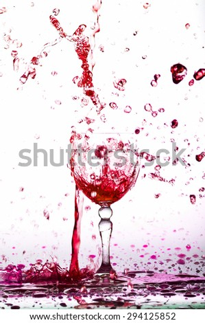 red wine splash in the glass on white background? water drop splash on white background