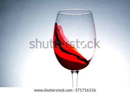 Red wine  splash in the wineglass, wine glass - stock photo
