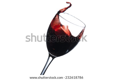 Red wine splashes pouring into moving wine glass isolated on a white background