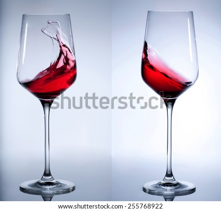 Red wine splashing in the elegant wine glass on gray background - stock photo