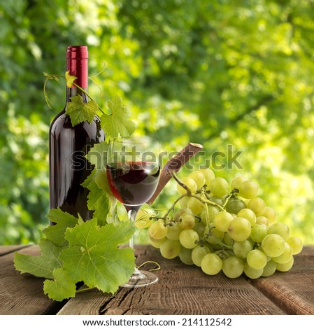 red wine, vine leaves and grape on wooden table - stock photo