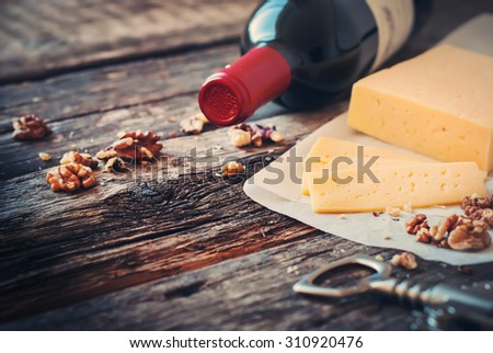 Red Wine, Walnuts and Cheese on Wooden Table. Rural Style - stock photo
