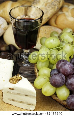 Red wine with some grapes,cheese and bread. - stock photo
